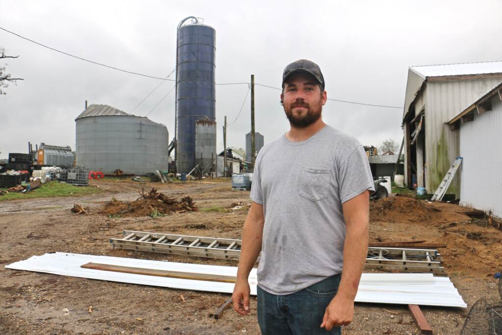 Eric Eachus stands amid the ruins caused by a tornado