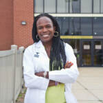 Dr. Ala Stanford stands in front of a health clinic with her arms crossed