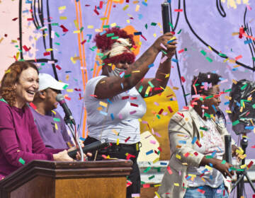 Mural Arts' executive director, Jane Golden (left), with mural models Tazmere Stephens (second from left) and Jourdyn Wood (second from right) and artist Kah Tangi, celebrate the dedication of We Are Universal to Philadelphia's trans community