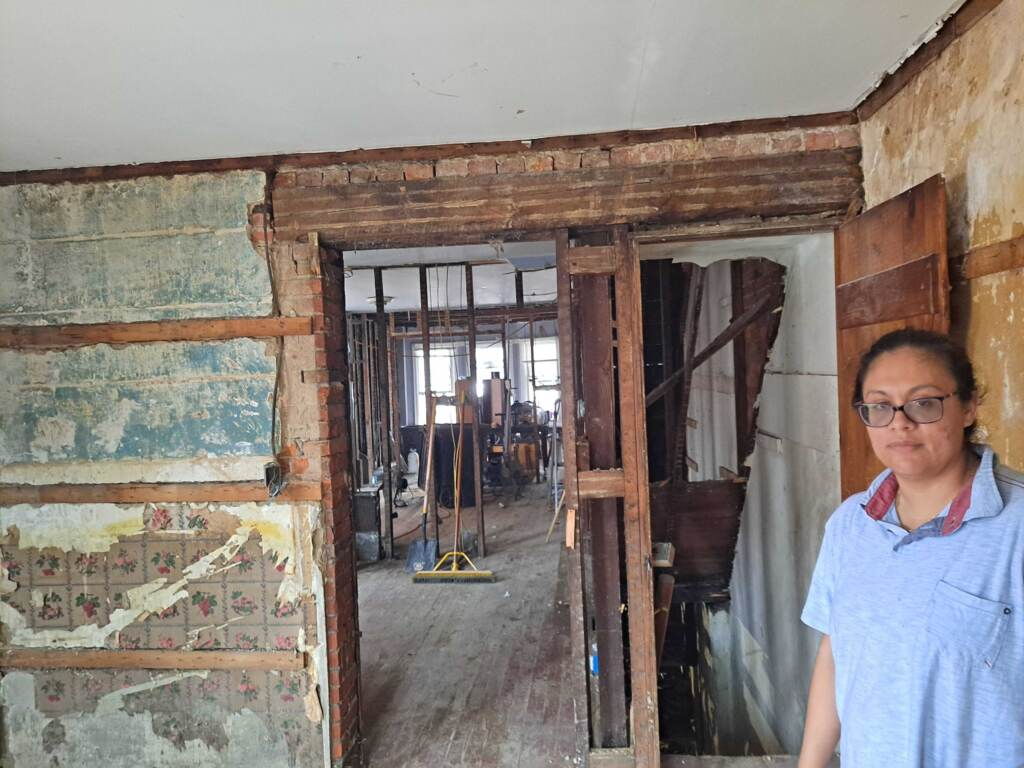 Person stands in damaged house.