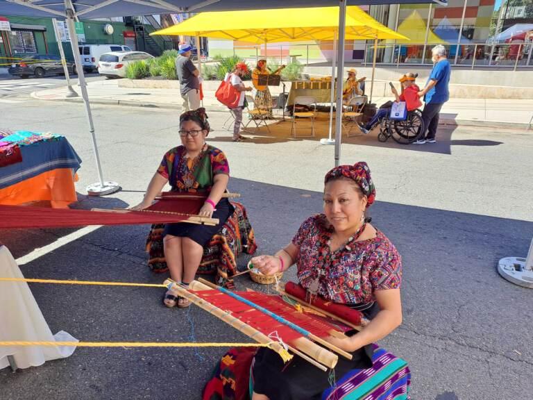 Two people showcase Guatemalan weaving.