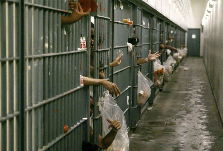 In this file photo, arms and hands of people in an LA County jail are seen through barred doors. (AP Photo/Damian Dovarganes, File, Pool)