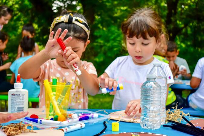 Two young girls coloring outside