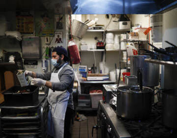 A kitchen worker wears a surgical mask and gloves as he prepares food