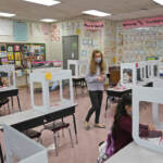 Maria Mirkovic works with some of her third graders in her classroom