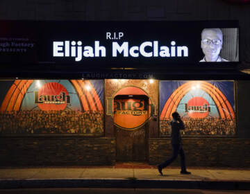 FILE - In this Aug. 24, 2020, file photo, a man walks past a display showing an image of Elijah McClain outside Laugh Factory during a candlelight vigil for McClain in Los Angeles.   Colorado's attorney general said Wednesday, Sept. 1, 2021 that a grand jury indicted three officers and two paramedics in the death of Elijah McClain, a Black man who was put in a chokehold and injected with a powerful sedative two years ago in suburban Denver. (AP Photo/Jae C. Hong, File)