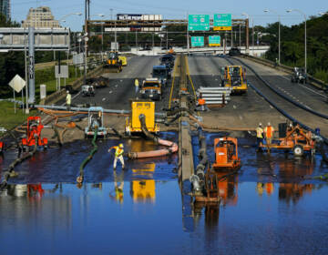 Workers pump water from a flooded section of Interstate 676 in Philadelphia Friday, Sept. 3, 2021