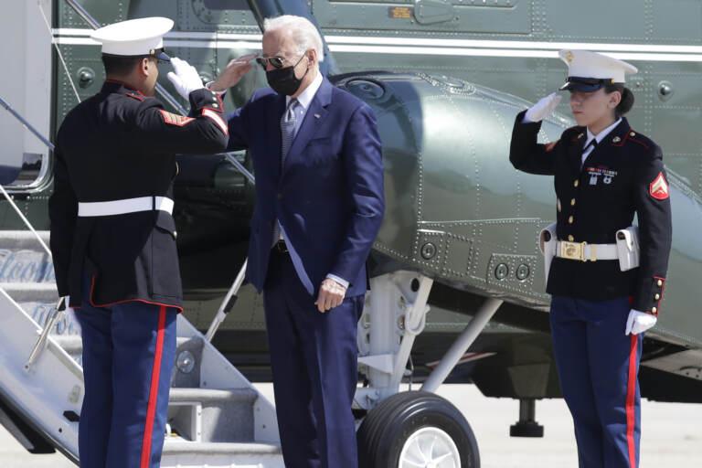 President Joe Biden returns a salute with a Marine Corp honor guard as he disembarks Marine One before boarding Air Force One