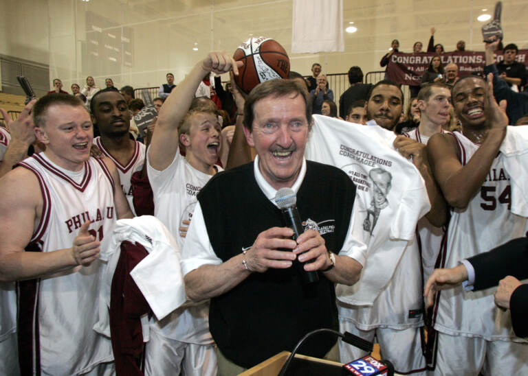 FILE - In this Feb. 1, 2007, file photo, Philadelphia University coach Herb Magee, center, celebrates his 829th career coaching victory, a new NCAA Division II record, with members of the team after they defeated Wilmington College, 65-60 in overtime, in an NCAA college basketball game in Philadelphia. Magee, who has 1,123 victories over a Basketball Hall of Fame career, will retire at the end of this season.  (AP Photo/Tom Mihalek, File)