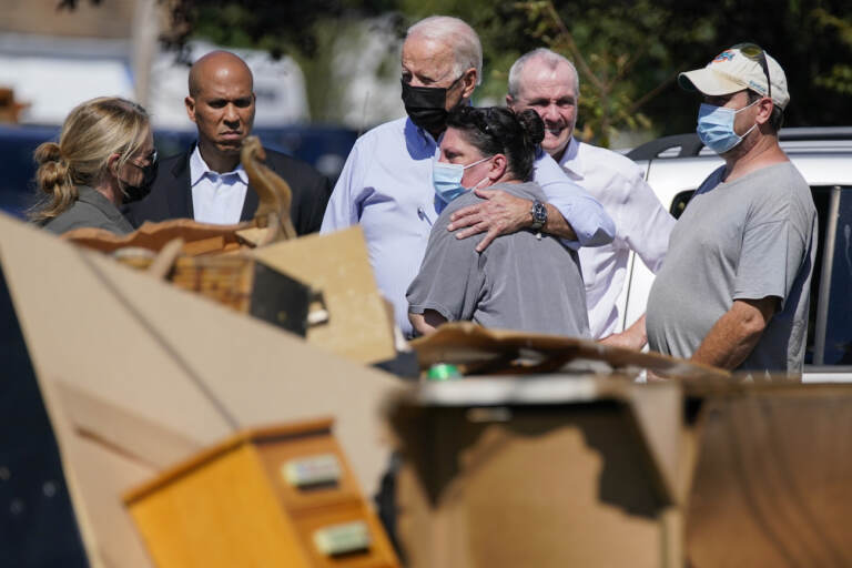 President Joe Biden hugs a person as he tours a neighborhood impacted by Hurricane Ida, Tuesday, Sept. 7, 2021, in Manville, N.J. Sen. Cory Booker, D-N.J., second from left, and New Jersey Gov. Phil Murphy, second from right, look on. (AP Photo/Evan Vucci)