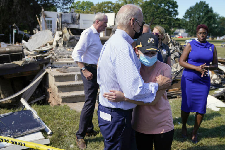 President Joe Biden talks with a person as he tours a neighborhood impacted by Hurricane Ida, Tuesday, Sept. 7, 2021, in Manville, N.J. New Jersey Gov. Phil Murphy, left, and Somerset County Commissioner President Shanel Robinson, right, look on. (AP Photo/Evan Vucci)