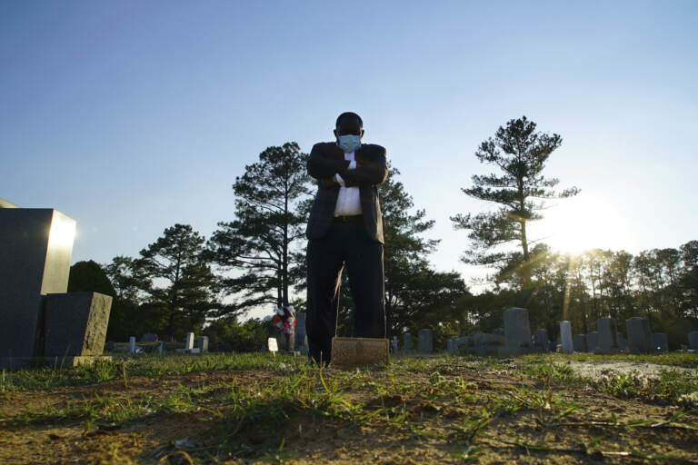 Mortician stands at a grave.