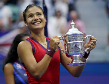 Emma Raducanu, of Britain, holds up the US Open championship trophy after defeating Leylah Fernandez, of Canada, during the women's singles final of the US Open tennis championships, Saturday, Sept. 11, 2021, in New York