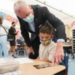 New Jersey Gov. Phil Murphy talks to a student in a pre-K class at the Dr. Charles Smith Early Childhood Center, Thursday, Sept. 16, 2021, in Palisades Park, N.J. Murphy toured the school before announcing plans to plans to provide universal pre-K for all families in New Jersey. (AP Photo/Mary Altaffer)