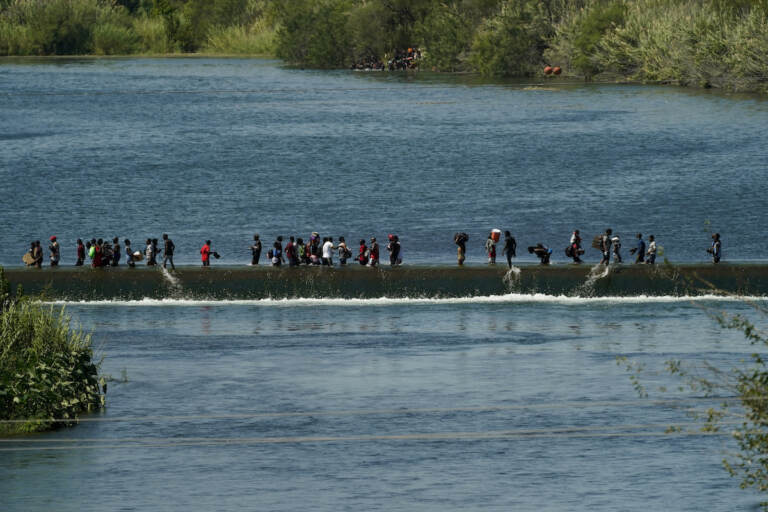 Haitian migrants use a dam to cross to and from the United States from Mexico, Friday, Sept. 17, 2021, in Del Rio, Texas