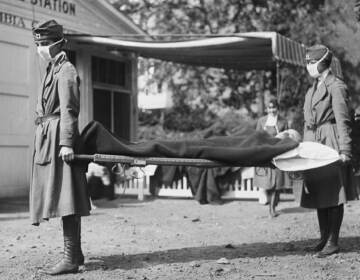 Two people hold either ends of a gurney during the 1918 pandemic