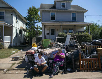 N.J. residents sit alongside belongings damaged by the remnants of Hurricane Ida outside their home