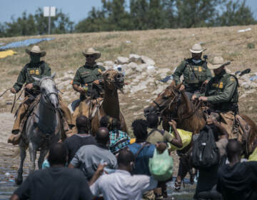 U.S. border patrol officers are seen on horses, with Haitian migrants pictured crossing the Rio Grande below
