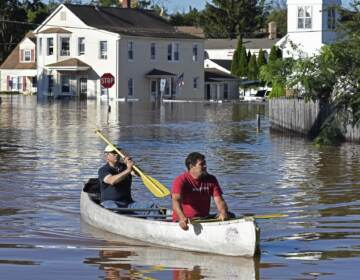 Residents canoe through floodwater