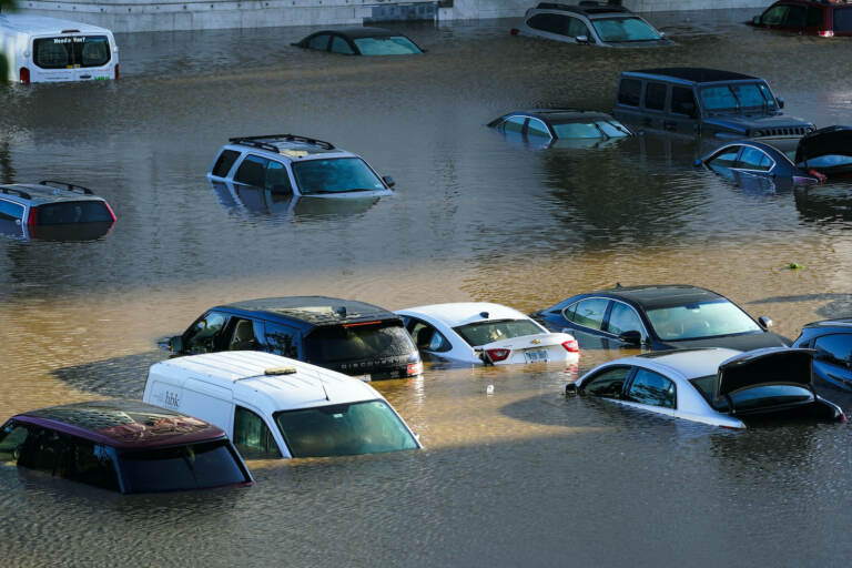 Vehicles are under water during flooding in a Philly parking lot