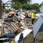 Utility workers work among debris from flood damage