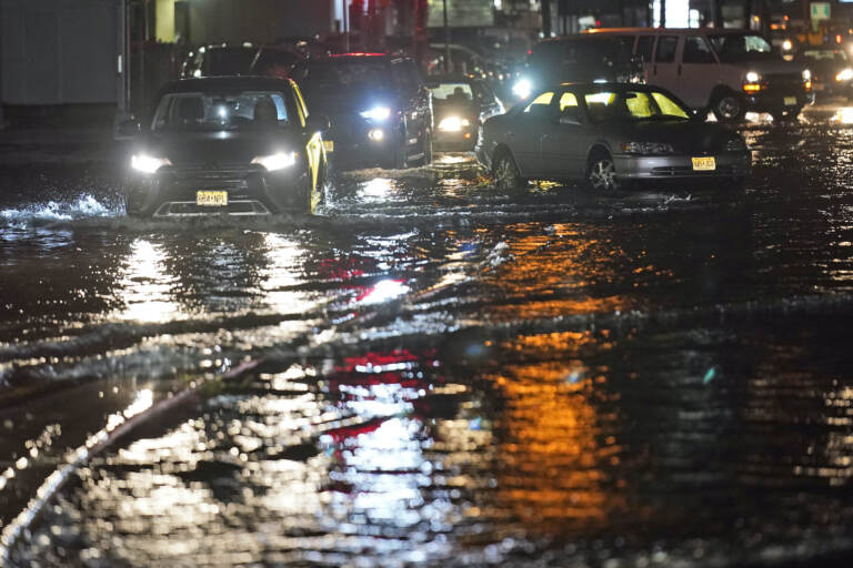 Cars make their way through flooded streets and around abandoned cars in Teterboro