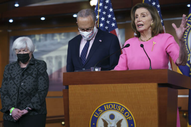 Nancy Pelosi stands at a podium, with Chuck Schumer and Janet Yellen standing to her right