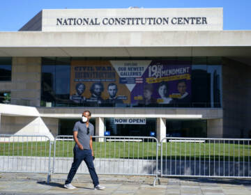A man walks past the National Constitution Center while wearing a mask