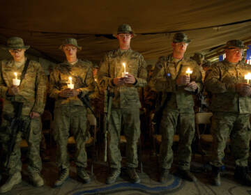 Soldiers hold up candles during a 9/11 anniversary event