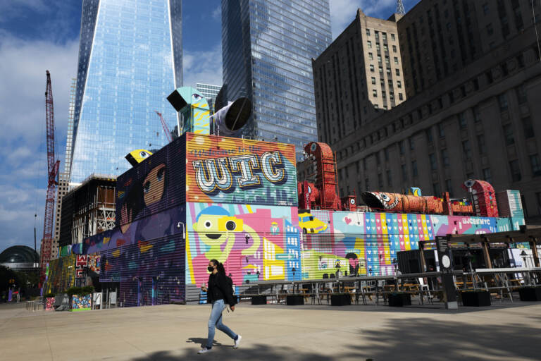 A woman walks by the colorful murals that surround the foundation for 2 World Trade Center
