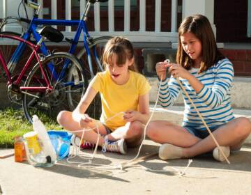 Two girls using rope to create an educational project outside