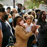 A crowd gathers outside Chester police headquarters, where the family of Bahir Green held a press conference to demand answers about the 16-year-old's arrest. A video appeared to show Chester police beating the boy after he surrendered. (Emma Lee/WHYY)