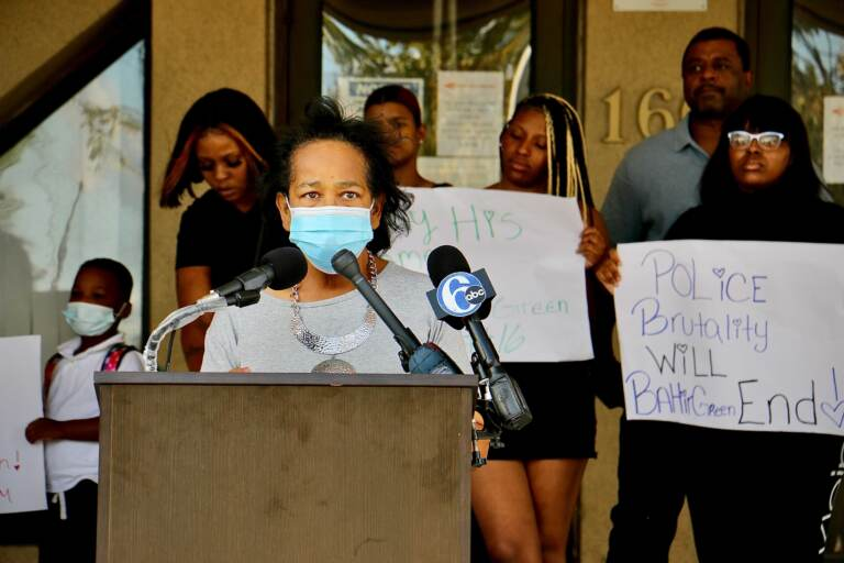 Zulene Mayfield, wearing a mask, speaks at a press conference
