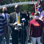 """Attorney Ben Crump joined by Micah """"Dew"""" Tennant's parents Samuel Dunmore (left) and Angela Tennant along with Micah's aunt Monica Tennant (far right) as he announces a lawsuit against the Pleasantville Board of Education and NJSIAA. (P. Kenneth Burns/WHYY)"""