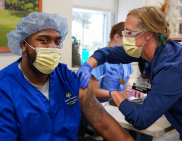 Kaylin Satterfield, a Christiana Care health aide, gets the COVID-19 vaccine on Thursday from from nurse manager Elizabeth Intermoia at Wilmington Hospital. (Courtesy of ChristianaCare)
