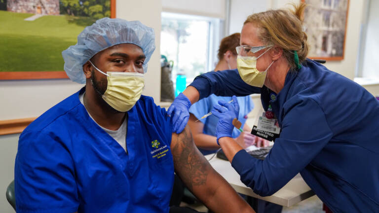 Kaylin Satterfield, a Christiana Care health aide, gets the COVID-19 vaccine on Thursday from nurse manager Elizabeth Intermoia at Wilmington Hospital. (Courtesy of ChristianaCare)
