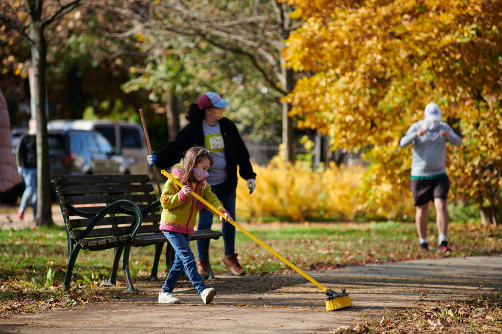 A young girl pushes leaves with a broom at a Philly park