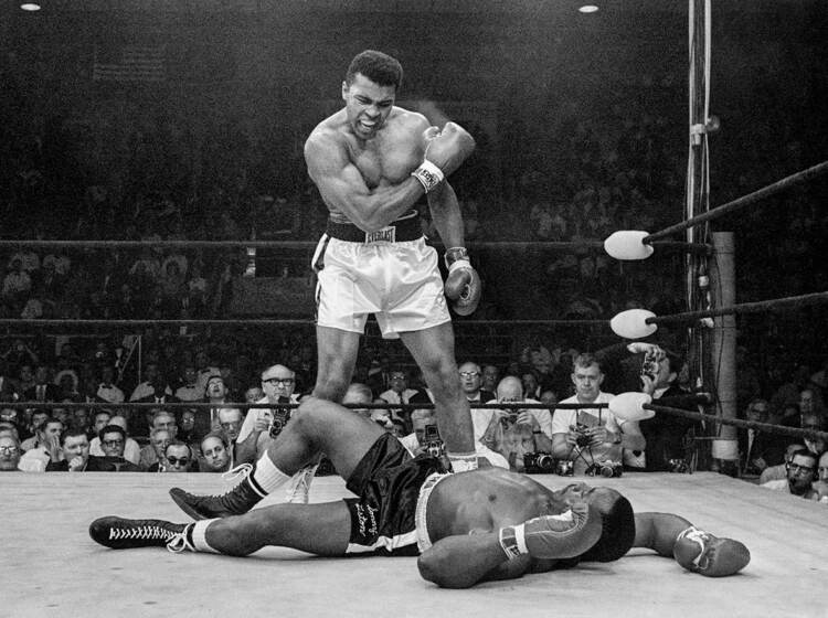 Muhammad Ali stands over fallen challenger Sonny Liston, shouting and gesturing
