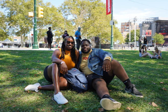 Mikaila Douglass, 22, and Boris Fabre, 23, sit under the shade as they wait for the first act to perform