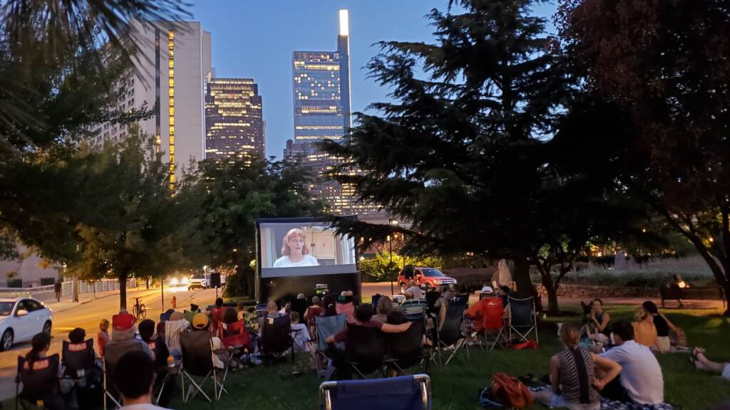 People sit on a park lawn to watch a movie on a projector screen