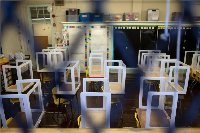Spaced out desks are pictured through a fence