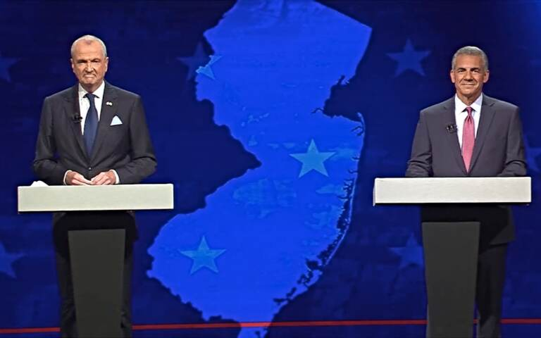 Gov. Phil Murphy (left) and ack Ciattarelli stand at podiums on opposite sides of a stage