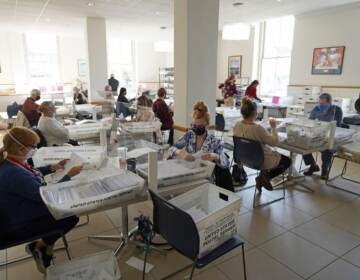 People sit at tables in a room with ballots from the 2020 election