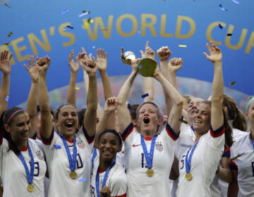 In this July 7, 2019, file photo, United States' Megan Rapinoe lifts up a trophy after winning the Women's World Cup final soccer match between U.S. and The Netherlands at the Stade de Lyon in Decines, outside Lyon, France. (Alessandra Tarantino/AP)