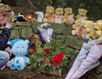 A mourner kneels beside 26 teddy bears, each representing a victim of the Sandy Hook Elementary School shooting, at a sidewalk memorial in 2012 in Newtown, Conn. (David Goldman/AP)
