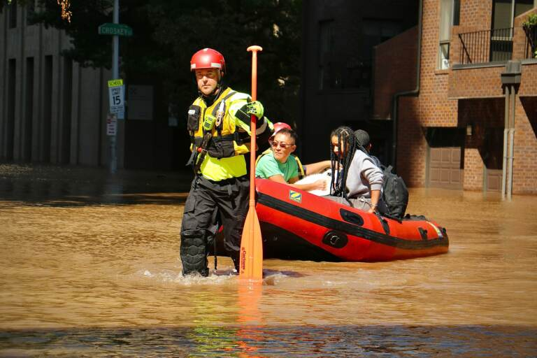 Philadelphia Fire Department personnel carry residents of the River Walk apartments to dry land