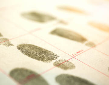 A criminal record with suspect fingerprints with a lens flare and cinematic tone