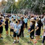 Kids, wearing masks, are surrounded by confetti outside during a ceremony