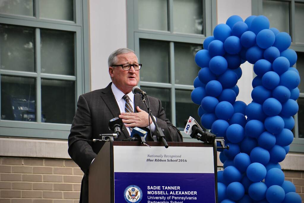 Jim Kenney gestures at a podium with a blue ribbon balloon display to his left