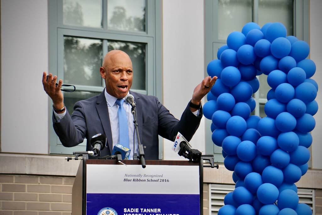 William Hite gestures at a podium with a blue ribbon balloon display to his left